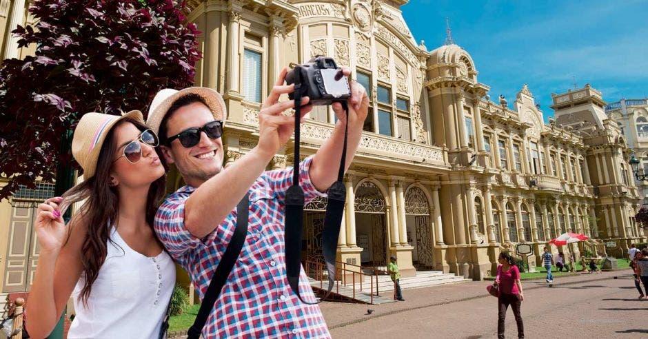 foto de dos jóvenes tomándose un selfie frente a correos de Costa Rica