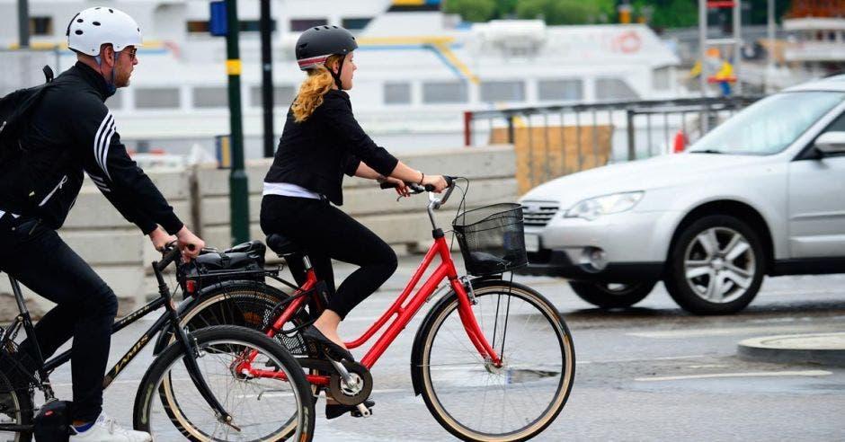 Dos personas andan en bicicleta por una calle poco concurrida