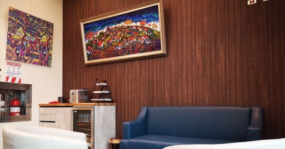 Una sala de espera adornada con dos cuadros y sillones de tela