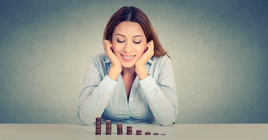 mujer feliz por ver sus grupitos de monedas crecer
