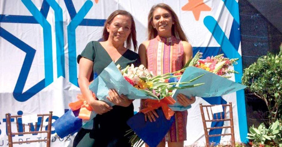 Dixinia junto a su hija Noelia Vargas con dos ramos de flores en el acto previo al festival de la luz