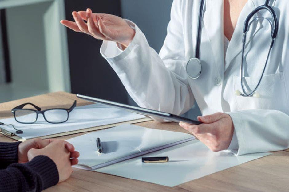 doctora sentada con análisis frente a un paciente