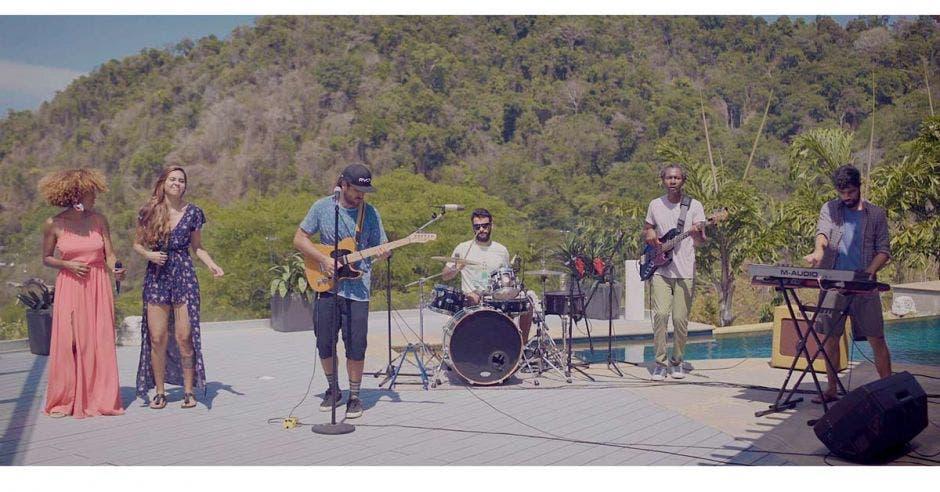 El grupo Earthstrong en una playa con toda su banda tocando uno de sus éxitos
