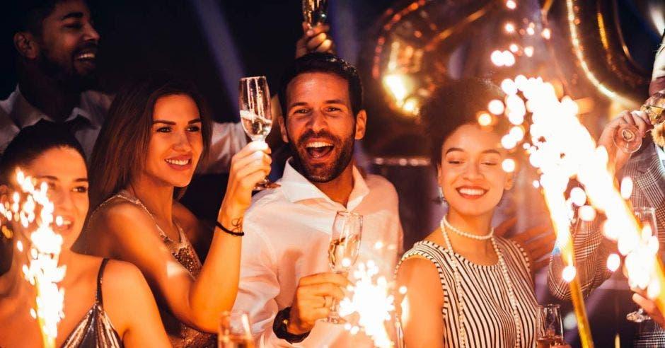 Varias personas disfrutando de una fiesta con copas de champagne y juegos artificiales