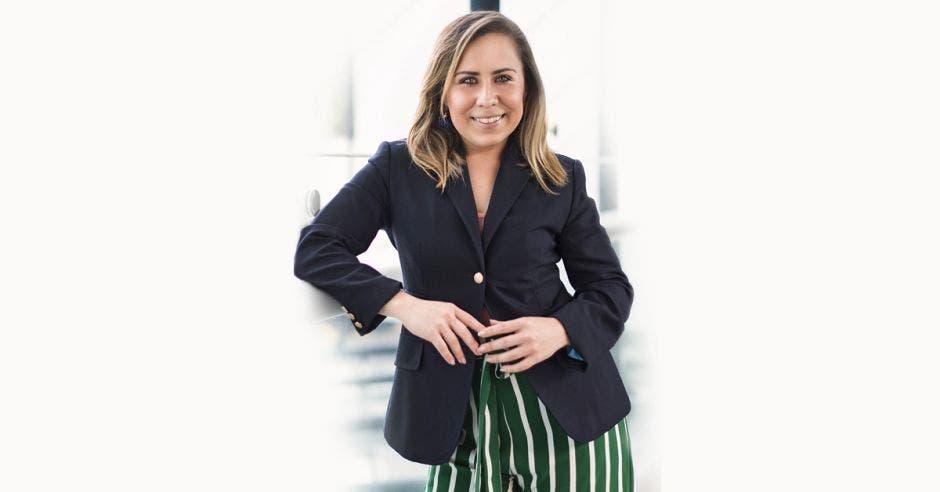 La confundadora de la firma con una blusa manga negra y un pantalón verde con rayas blancas