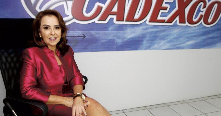 Laura Bonilla posa sentada en una silla con el letrero de Cadexco de fondo