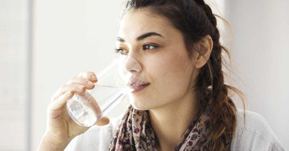 Una mujer morena joven toma agua de un vaso