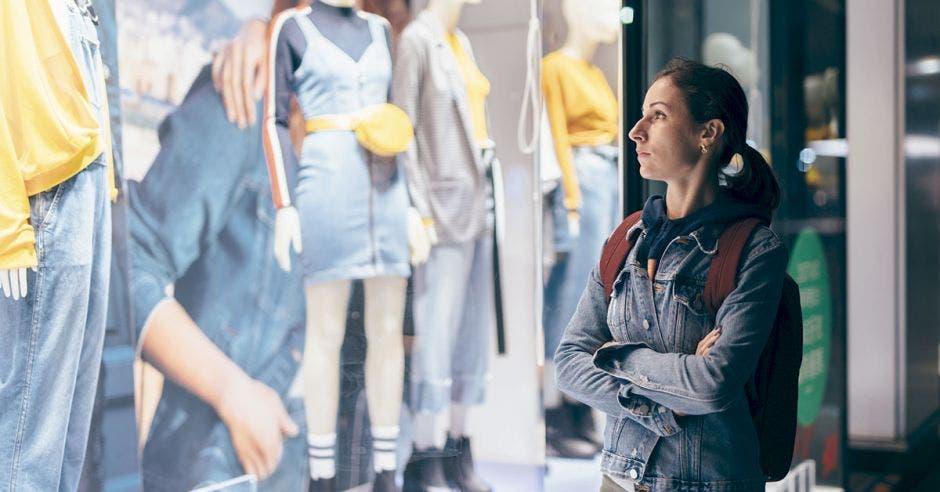Mujer observa una ventana de una tienda de ropa con una expresión triste