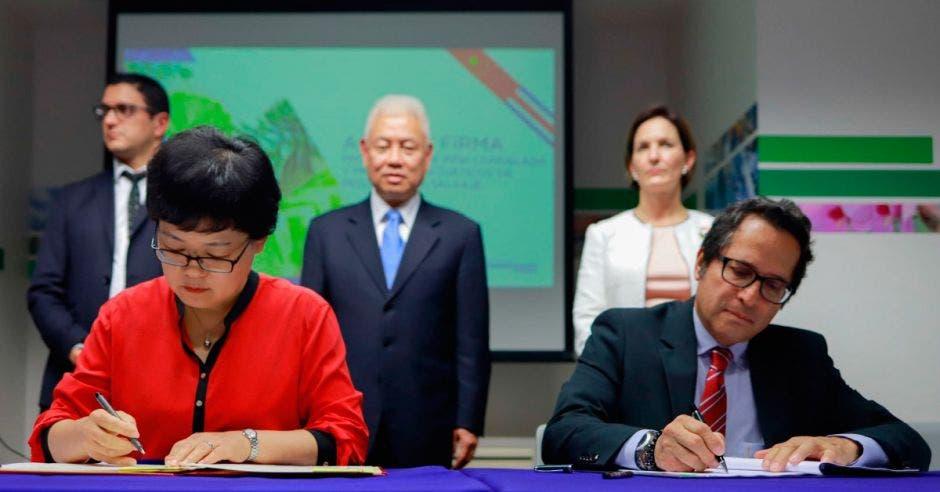 dos personas firman documentos sentados en una mesa, atrás tres personas de pie