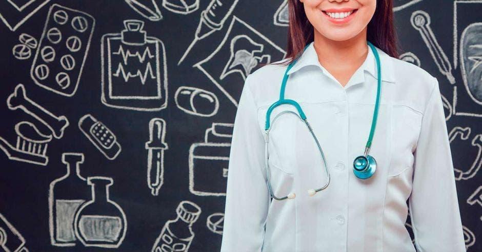 doctora con pizarra negra de fondo con dibujos médicos