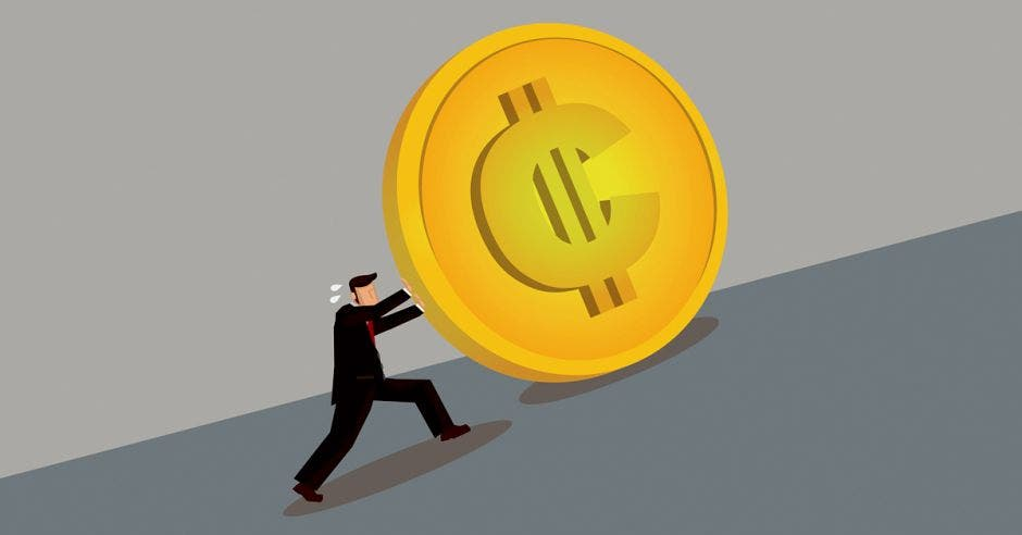 persona empujando una moneda con signo de colón en una cuesta