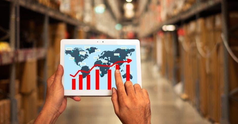 Persona con un iPad revisa la dirección de las cajas de exportación que tiene en una bodega