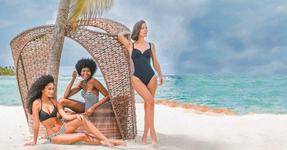 Tres mujeres conb con trajes en una playa un poco nublado