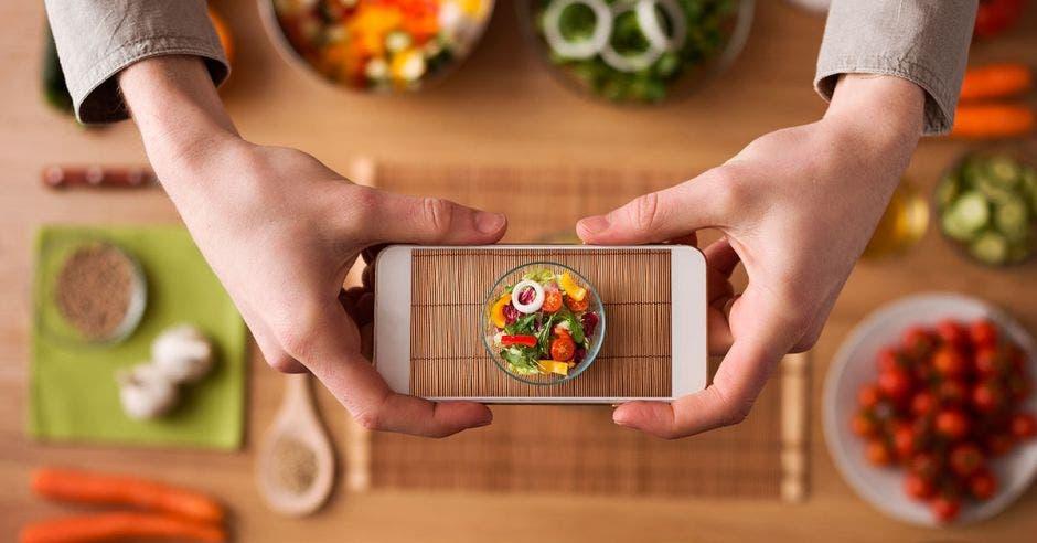 Unas manos tomando una foto con el celular a un platillo de comida