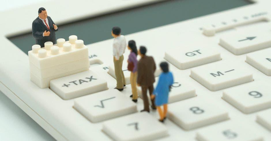 Personas de juguete haciendo fila para pagar impuesto encima de una calculadora con lego y la palabra tax en las teclas