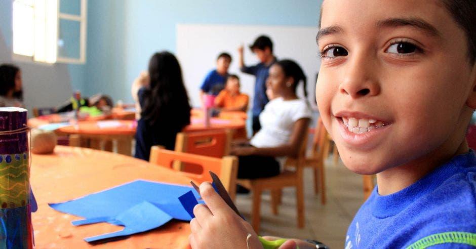 Un niño en una clase sonriente mientras hace unos recortes