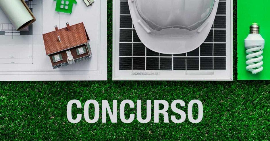 Una casita mini, planos y un casco de construcción en un zacate artificial