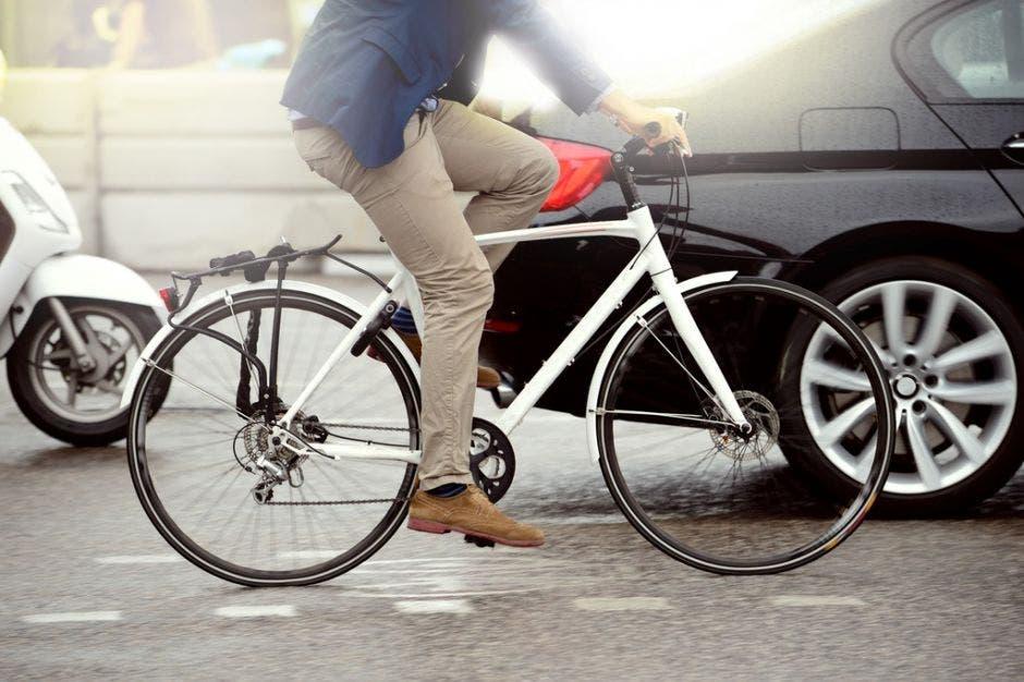 persona en bicicleta y un auto de fondo