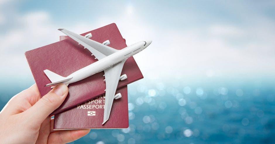 cielo azul y mar de fondo y mano sostiene un avión de juguete y dos pasaportes en primer plano