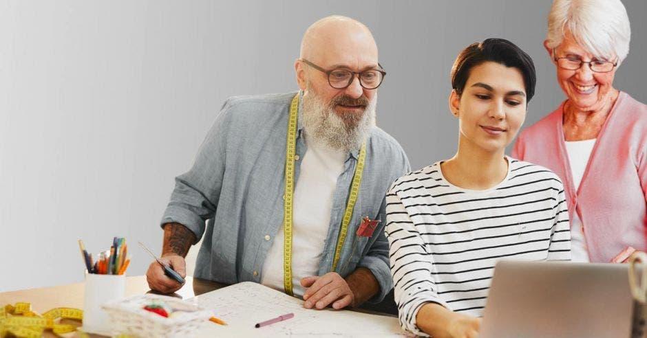 Una pareja de adultos revisa un avance en la computadora junto a una muchacha