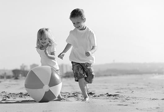 Una pareja de niños juega con una pelota en la playa