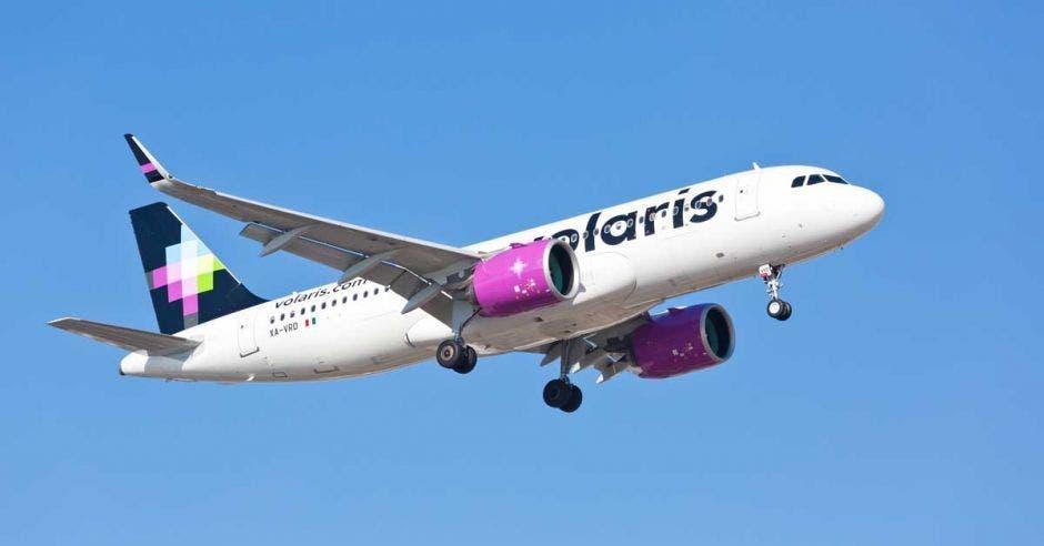 Un avión de volaris color blanco y detalles en rosa y azul