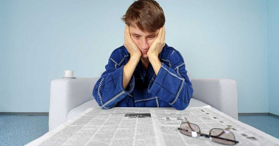 Un hombre mira decepcionado el periódico en busca de empleo
