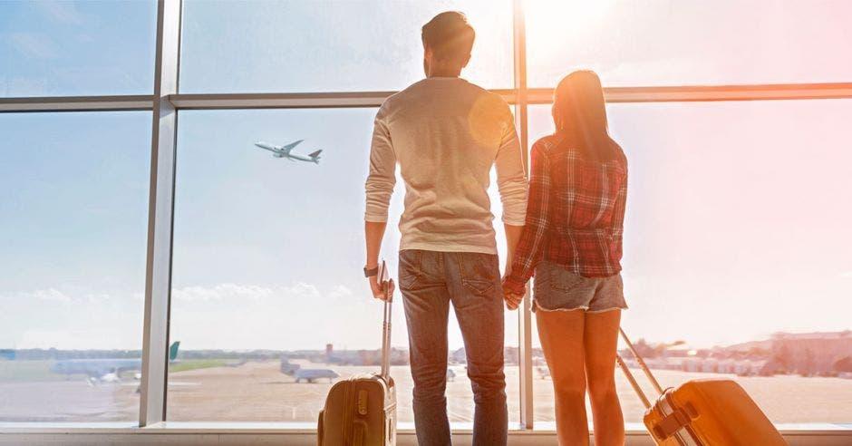 Una pareja sostiene un par de maletas en una sala de abordaje