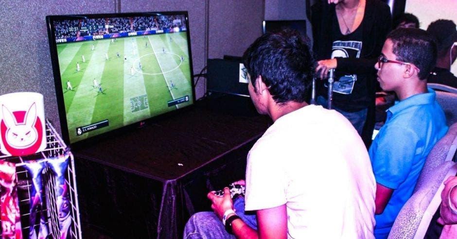 Dos jóvenes juegan un videojuego de fútbol