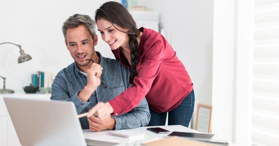 pareja señala computadora