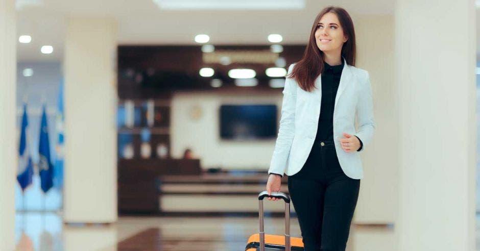 Una mujer con una valija camina por los pasillos de un hotel