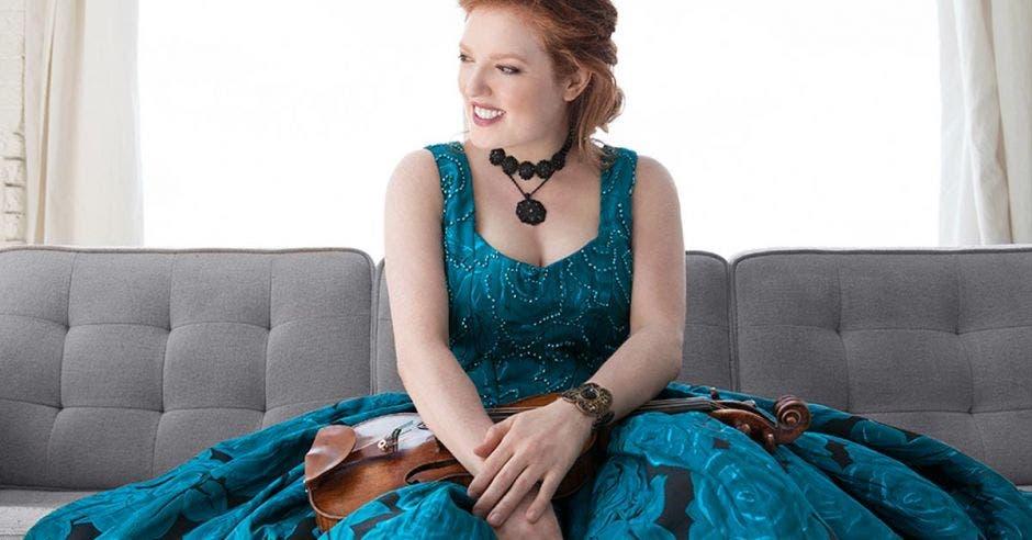 La violinista con un vestido turquesa y un violín entre sus brazos