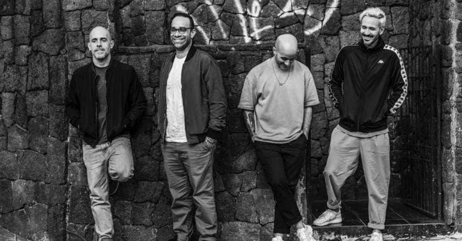 Los 4 intengrantes de la banda en blanco y negro, riendo arrecostados en una pared