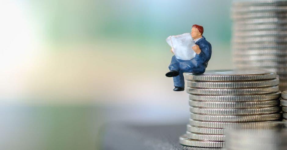 Persona empresaria sentada sobre una columna de monedas