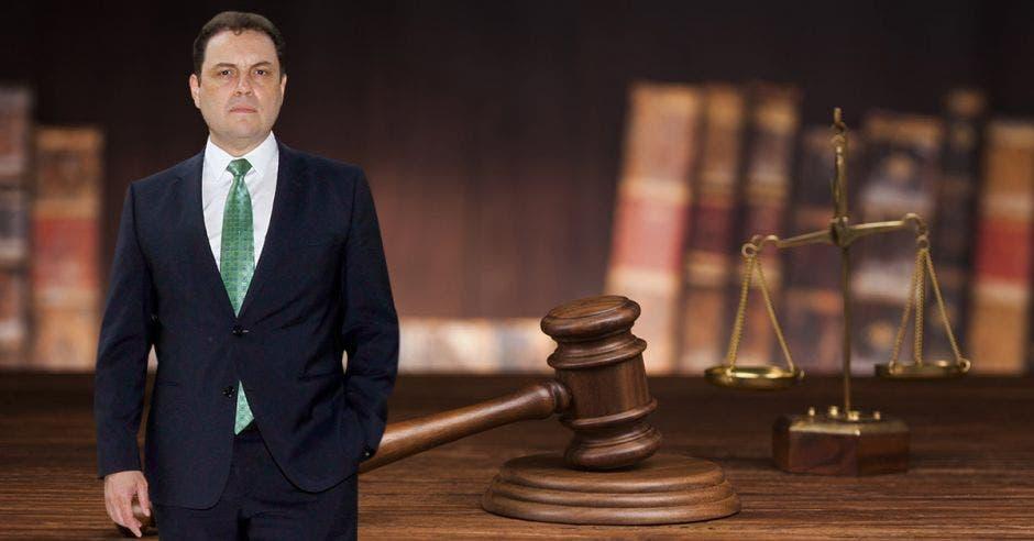 Carlos Ricardo Benavides de frente y unos libros de derecho