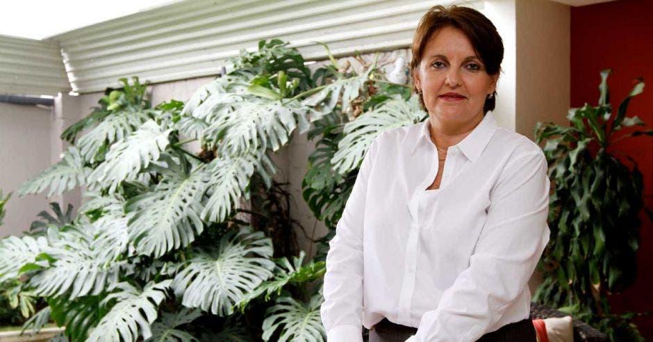 Una mujer con blusa blanca posa en un jardín