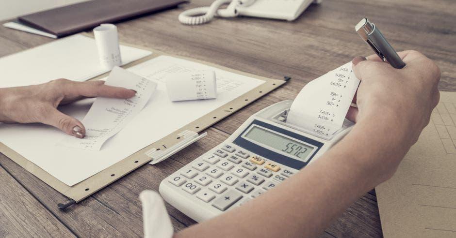 Mujer sacando cuentas con una calculadora