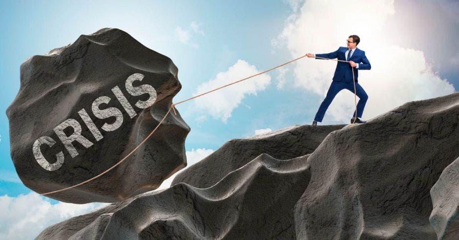 persona jalando una piedra con la palabra crisis