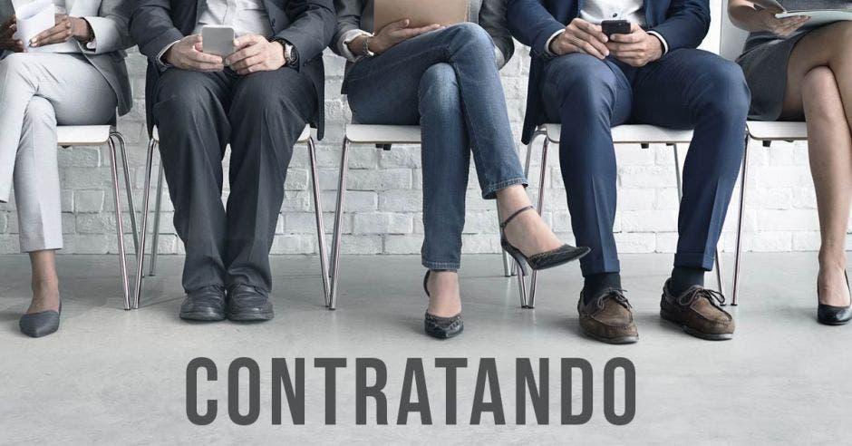 Unas personas sentadas esperando y la palabra contratando
