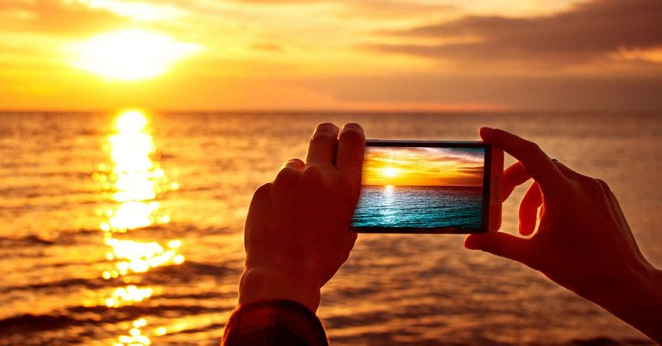 Alguien fotografía la puesta de sol en el horizonte