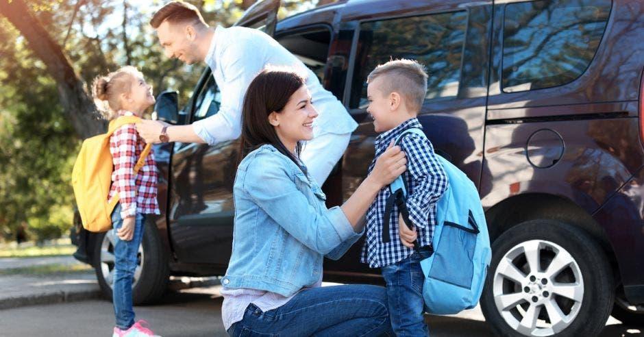 Familia deja a sus hijos a la escuela