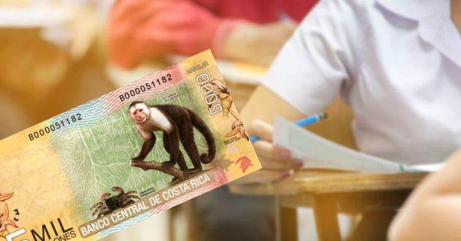 Un billete de ¢5 mil y unas personas haciendo examen
