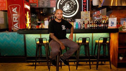 El gerente sentado en una silla de su restaurante con una camisa negra, pantalones grises y tennis