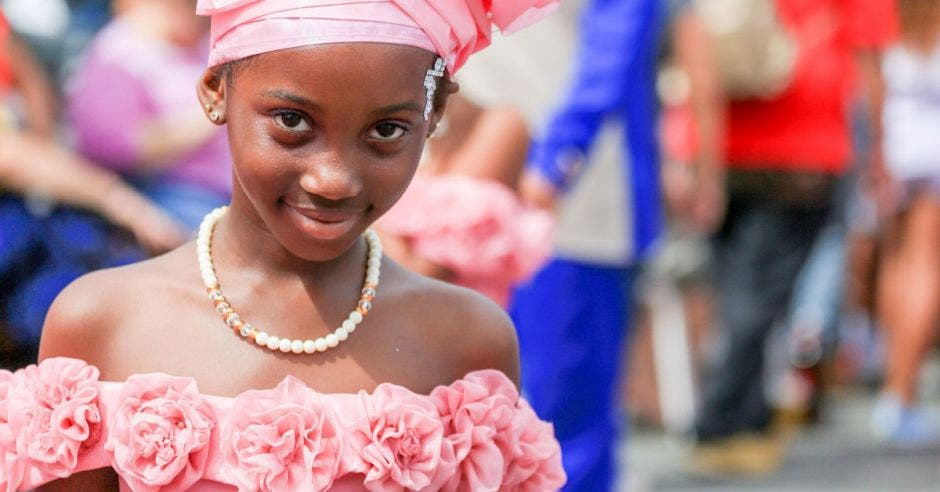 Una niña afrodescendiente con un vestido de color rosado, en una actividad cultural