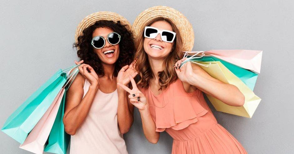 Dos mujeres de compras, con lentes negros y vestimentas de verano blanco y rosado