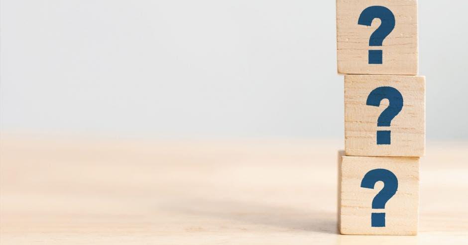 cuadros de madera con signos  de pregunta apilados  en una torre