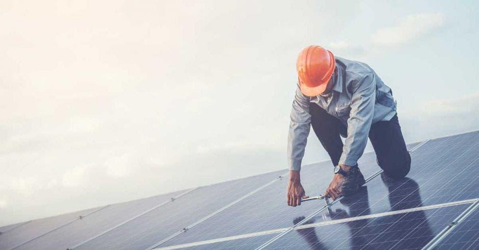 Un señor de mediana edad instala paneles solares