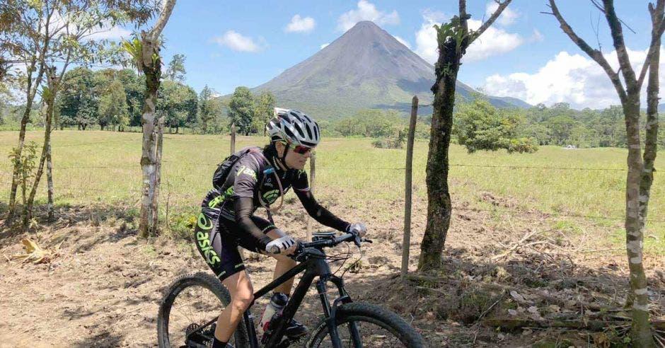 Uno de los participantes de la competencia pedaleando en su bicicleta con el volcán Arenal de fondo