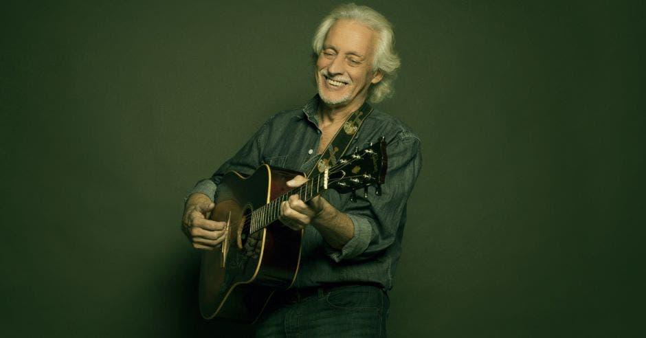 Nito Mestre tocando su guitarra mientras sonríe