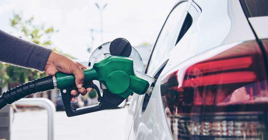Una persona llena de combustible su vehículo
